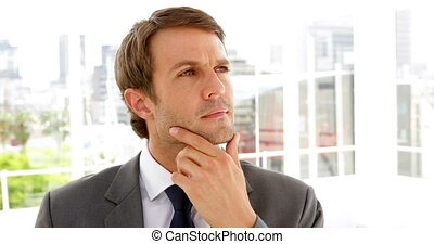Thinking businessman standing in his office