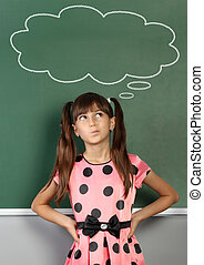 Thinking child near school blackboard with blank speech bubble