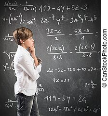 Thinking child with mathematical problem in the blackboard