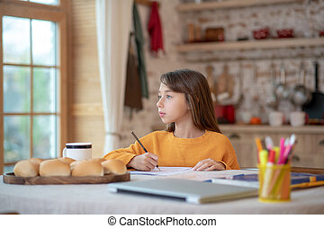 Cute girl in orange shirt looking thoughtful