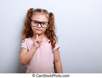 Thinking cute kid girl looking confident in eyeglasses on blue background