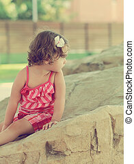 Thinking cute kid girl looking on big stone outdoors background