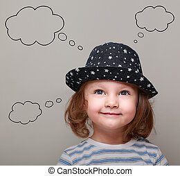 Thinking cute kid girl with many ideas in empty bubble on grey background looking up