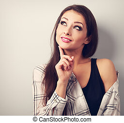 Thinking fun casual smiling young woman looking up. Toned closeup portrait