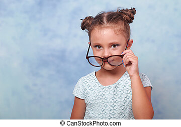 Thinking fun kid girl in glasses looking happy and holding eyeglasses the hand on blue background with empty copy space.