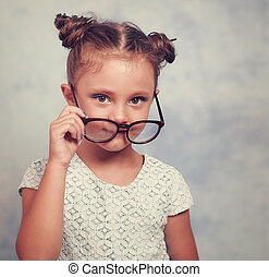 Thinking fun kid girl in glasses looking happy and holding eyeglasses the hand. Toned closeup portrait