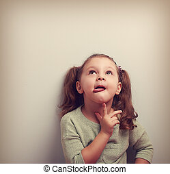 Thinking fun kid showing tongue looking up on copy space