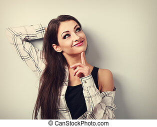 Thinking fun smiling young woman in casual clothing looking up. Toned portrait