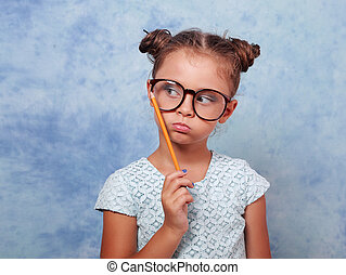 Thinking grimacing kid girl in glasses looking and holding pencil in hand on blue background with empty copy space