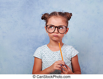 Thinking grimacing kid girl in glasses looking and holding pencil in hand on blue background with empty copy space.