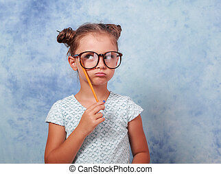 Thinking grimacing kid girl in glasses looking up and have an idea, holding pencil in hand on blue background with empty copy space