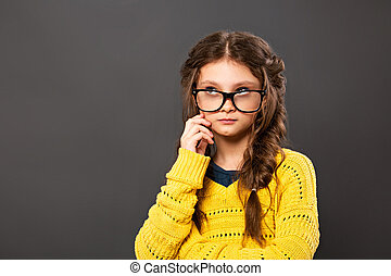 Thinking grimacing serious schoolgirl in eyeglasses looking up on grey studio background. Back to school. The concept of education.
