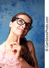Thinking happy girl in glasses looking up on blue background