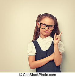 Thinking happy smiling pupil girl in fashion eyeglasses looking up with finger idea sign near the face in school uniform. Toned vintage portrait