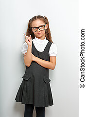 Thinking happy smiling pupil girl in fashion eyeglasses looking up with finger idea sign near the face in school uniform on blue background
