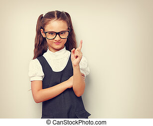 Thinking happy smiling pupil girl in fashion eyeglasses with finger idea sign near the face in school uniform. Toned vintage portrait