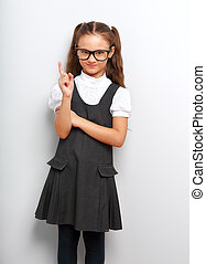 Thinking happy smiling pupil girl in fashion eyeglasses with finger idea sign near the face in school uniform on blue background
