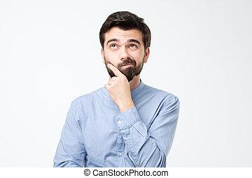 Thinking hispanic man isolated on white background.