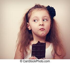 Thinking humor kid face eating chocolate. Closeup vintage -...