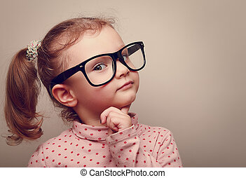 Thinking kid girl in glasses looking happy. Closeup...