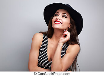 Thinking makeup woman in fashion hat looking up and dreaming about sales on blue background