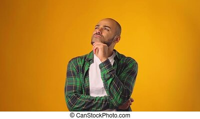 Thinking man looking up and touching his chin against yellow background. High quality FullHD footage
