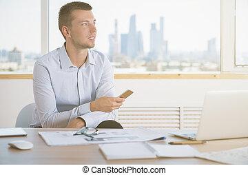 Thinking man using cellphone