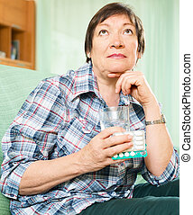 thinking mature woman with pills and glass of water