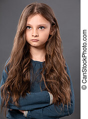 Thinking pupil kid girl with folded arms thinking and serious looking up on grey studio background. Closeup