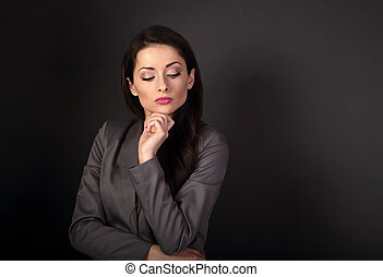 Thinking serious business woman in grey suit looking down on dark grey background with empty copy space