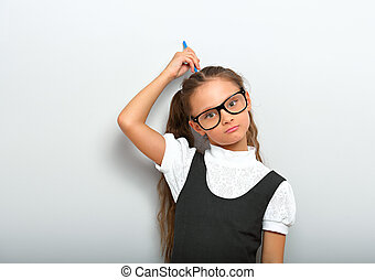 Thinking serious skeptical pupil girl in fashion eyeglasses in school uniform and scratching pencil the head on blue color background with copy empty space