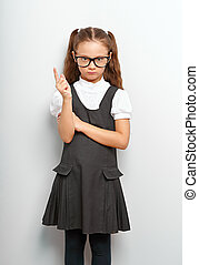 Thinking serious skeptical pupil girl in fashion eyeglasses with finger idea sign near the face in school uniform on blue background