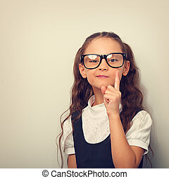 Thinking serious skeptical pupil girl in fashion eyeglasses with finger idea sign near the face in school uniform. Toned vintage portrait