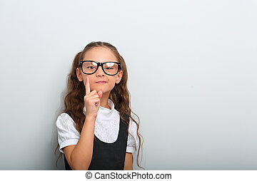 Thinking serious skeptical pupil girl in fashion eyeglasses with finger idea sign near the face in school uniform on blue background with copy empty space