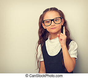 Thinking serious skeptical pupil girl in fashion eyeglasses with finger idea sign near the face in school uniform. Vintage toned portrait