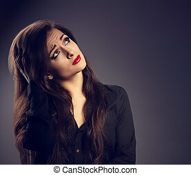 Thinking serious unhappy woman in shirt looking on grey empty copy space background. Toned portrait