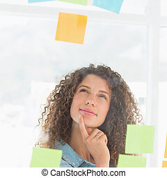 Thinking smiling designer looking at sticky notes on window