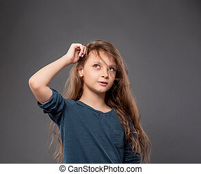 Thinking smiling grimacing kid girl scratching the head and looking up on grey studio dark background with empty copy space.