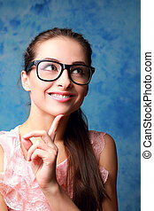 Thinking smiling woman looking up in modern glasses. Closeup portrait