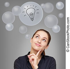 Thinking smiling woman looking up on many bubbles with idea bulb sign on grey background