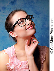Thinking student girl in glasses looking up on blue background