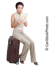 Thinking tourist woman looking at city map on suitcase isolated