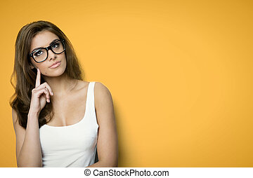 thinking woman with nerd glasses on a orange background