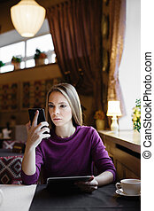 Thinking woman with phone