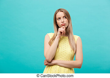 Thinking young confident woman in yellow dress looking up isolated on blue background