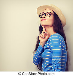 Thinking young happy woman in hat and glasses looking up. Bright vintage portrait