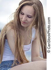 Thinking young model woman sitting outdoor