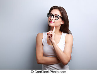 Thinking young woman in glasses looking on empty space background