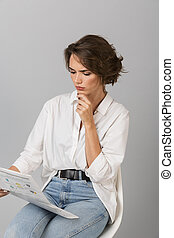 Thinking young woman sitting on stool isolated over grey background.