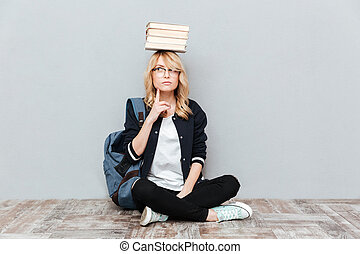 Thinking young woman student holding books on head.
